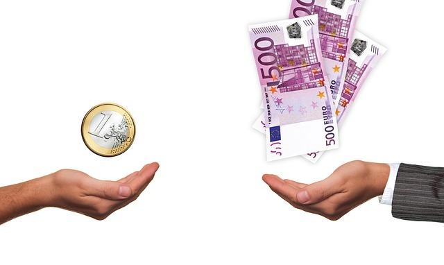 dvě ruce – s bankovkami a mincí