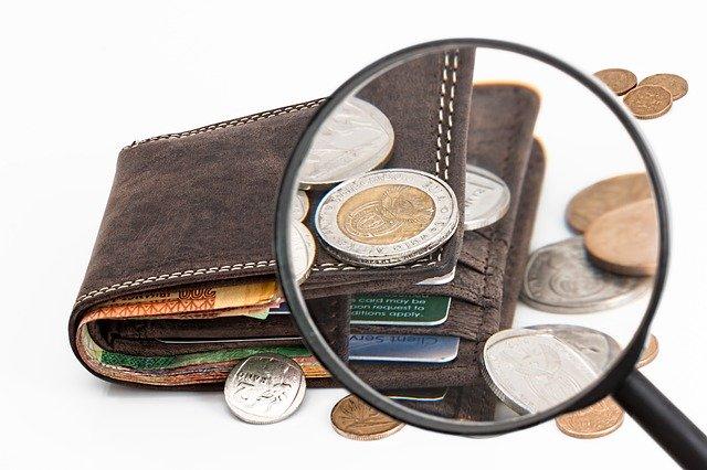 peníze v peněžence pod lupou